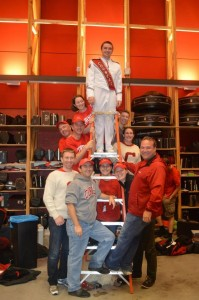 Big Red Drum Majors, past and present, pose on the ladder during Homecoming, Fall 2013.